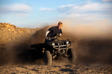 atv: teen riding ATV quad - four wheeler kicking up dirt