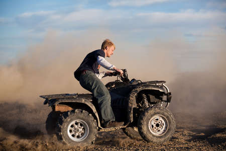 wheeler: teenager riding ATV quad - four wheeler in the hills kicking up dirt