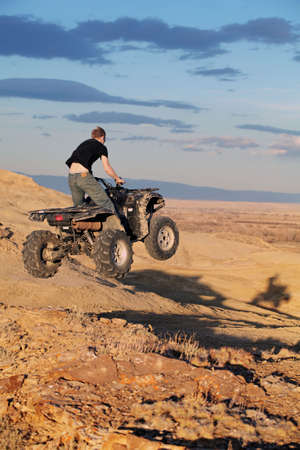 getting late: Teenager jumping on a quad ATV in late sun - four wheeler getting air in the hills of Wyoming