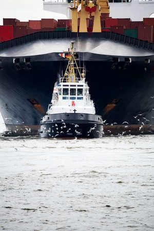 the boat on the river: remolcador tirando de un carguero en el r�o Elba en Hamburgo puerto, Alemania