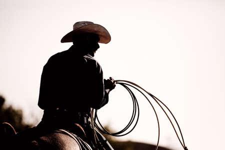 rodeo americano: vaquero con lazo a caballo en el rodeo - silueta con adici�n de grano Foto de archivo