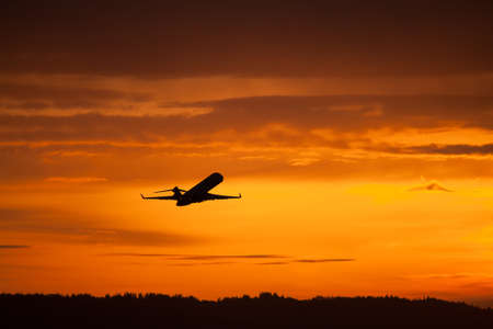 corporate jet: airplane taking off in sunset