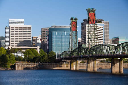 Portland Oregon skyline with Hawthorne bridge crossing the Willamette river under clear blue sky