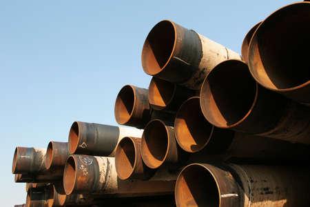 rusting: Pile of rusting steel industrial pipes under clear blue sky
