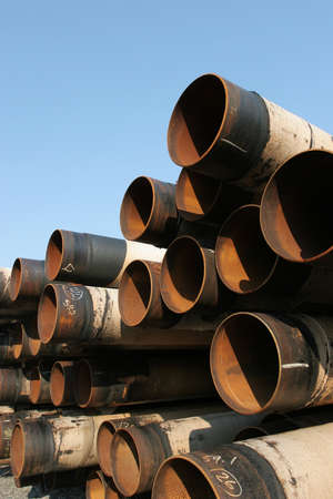 rusting: Pile of large industrial steel pipes rusting under clear blue sky Stock Photo