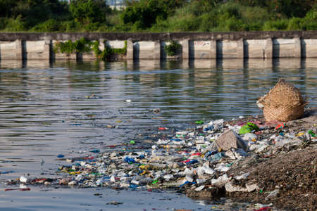 Water pollution - heavily polluted river inlet with various garbage along shore and floating on water. Manila, Philippines.