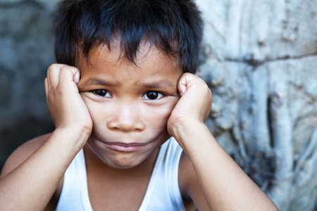 Young Asian male against wall - Poverty in the Philippines Stock Photo