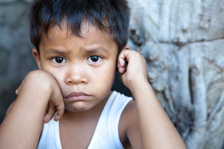 poor people: Poverty - portrait of a cute young Asian boy, Filipino male against wall with copyspace. Stock Photo
