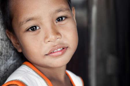 極貧地域 - 壁に対して縦に住んでいる柔らかい笑顔でアジアの若い男の子。マニラ、フィリピン。