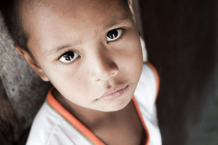 Portrait of a Filipino boy living in poverty - natural light - Manila, Philippines. Stock Photo