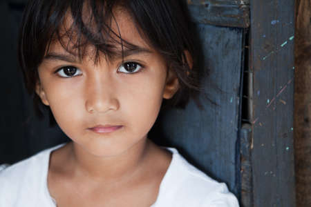 filipina: Portrait of an Asian girl against wall in natural light - Manila, Philippines Stock Photo