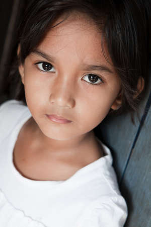 somber: Portrait of a pretty young girl from the Philippines against a wall