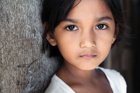 poor people: Portrait of a pretty 8 year old Filipina girl in poverty-stricken neighborhood, natural light.