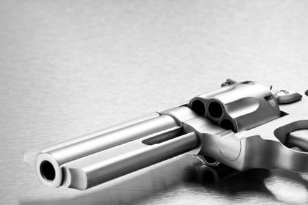 handgun on steel background - modern revolver closeup with copyspace. Focus on cylinder.