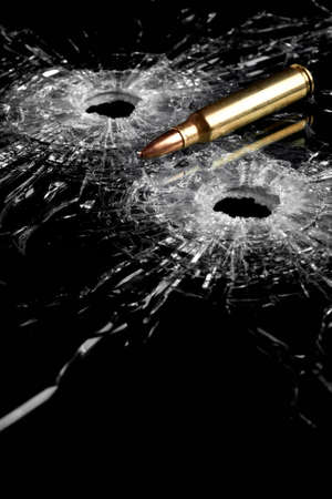 bullet holes in glass with bullet - broken glass isolated on black Stock Photo