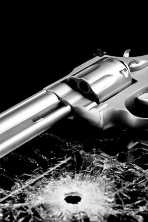 handgun with bullet hole in glass isolated on black - modern revolver with broken glass Stock Photo
