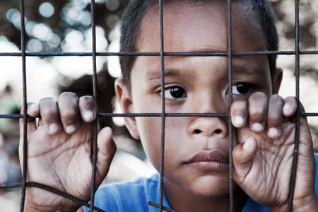 Asian boy behind and clinging to fence in the Philippines - contemplating look to the side - shallow dof with focus on face.