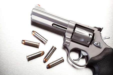 gun: gun with bullets on steel surface - modern revolver handgun