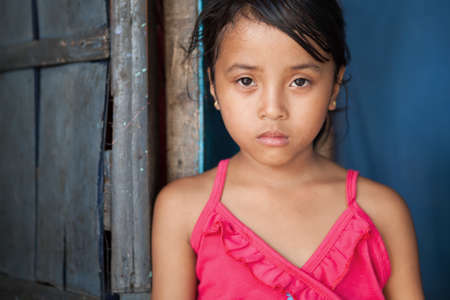 world thinking: Portrait of a young girl from poverty-stricken area in Manila, the Philippines.