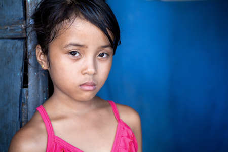 developing country: Young Filipina girl 8 years old with sad and somber expression over blue, poverty in the Philippines. Stock Photo