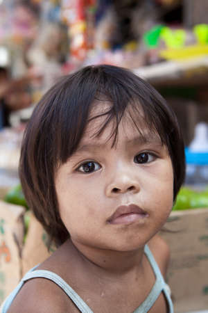 impoverished: Asian child from impoverished area - natural portrait by a local market in the Philippines.