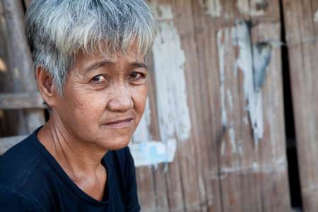 impoverished: Asian senior from an impoverished area, outside her home in the Philippines