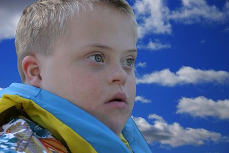 anticipating: Down Syndrome Boy with Head in the Clouds Stock Photo