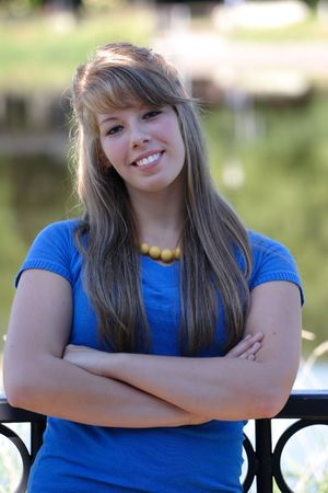 A beautiful teenage girl in a blue top with a yellow beaded necklace photo