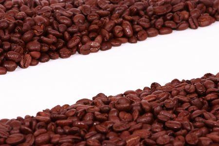Two Diagonal piles of coffee beans on white. photo
