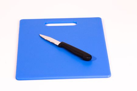 paring knife: A black handled paring knife resting at an angle on a blue cutting board. Isolated on a white background.