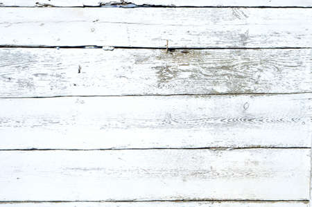 Grungy flaky white paint background on a wooden fence.