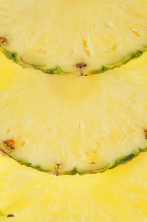 Round parts of pineapple as yellow background