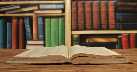 opened textbook on a bookshelves background Stock Photo