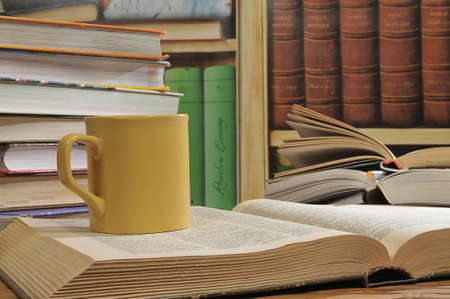 Large yellow cup of tea among the stack of books