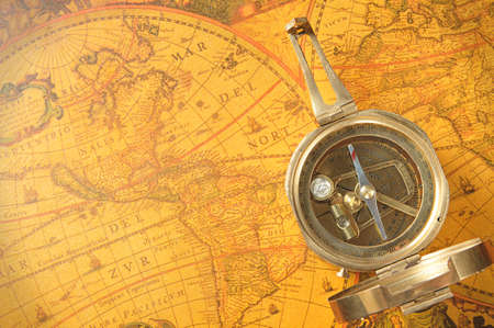 Old-age compass on antique world map