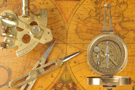 Old-fashioned navigation devices on antique world map Stock Photo
