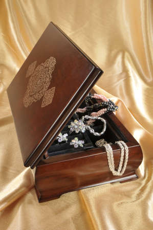 chainlet: Close-up of wooden box with jewelry on golden background