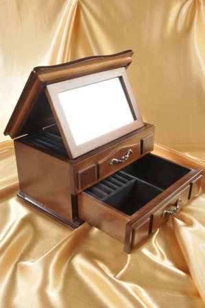 Close-up of wooden box for keeping valuables with mirror on golden background