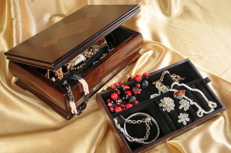 Wooden box with jewelry on golden background  Stock Photo