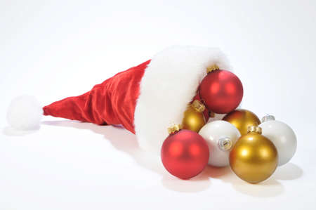 Multicolors christmas balls on the snow from Santa hat Stock Photo