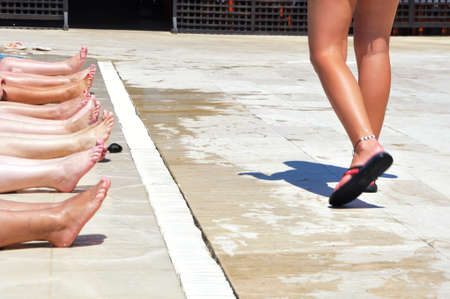 female feet on the edge of the pool waiting for instructions from the coach