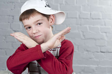 Portrait of a 10-year-old boy with crossed arms in the form X. Studio shoot. photo