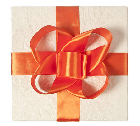 Bow of orange ribbon on the gift box in wrapping paper, isolatet on white. View from up. Stock Photo