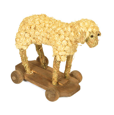 Straw and wood shaving toy lamb isolated on white background