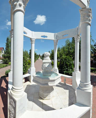 beautiful architectural structure of white stone fountain with flowing water from the open mouth of a lion