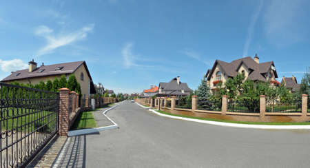 asphalted road, traveling among the beautiful homes in the exclusive town Stock Photo