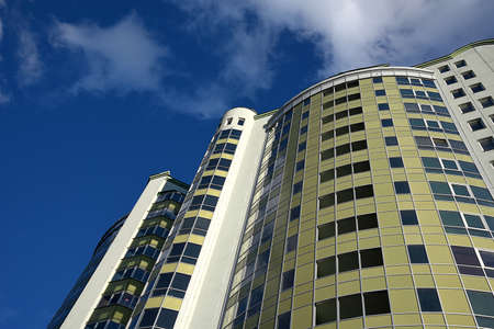 High-rise apartment building, shot from the perspective against the blue sky Stock Photo