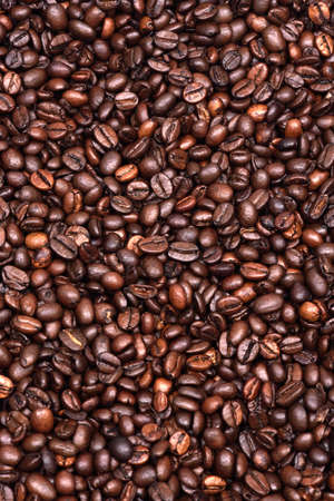 Roasted coffee beans scattered on the plane as a uniform background.