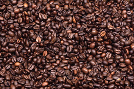 Roasted coffee beans scattered on the plane as a uniform background Stock Photo