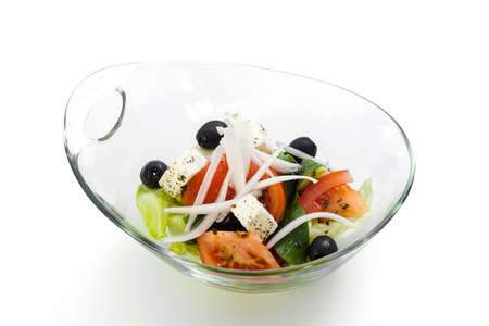 ingradient: Greek salad in a glass salad bowl on a white background. Stock Photo